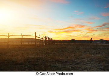 Old rustic fence in fields evening time