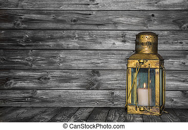 Old rustic golden lantern on wooden old shabby background...