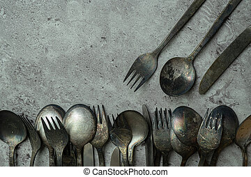 Old rustic style forks and spoons on grunge gray background