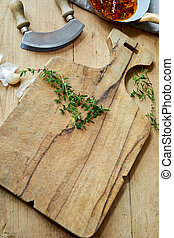 Old rustic wooden chopping board with herbs