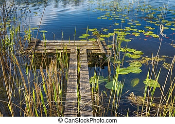 Old rustic wooden jetty on a tranquil lake