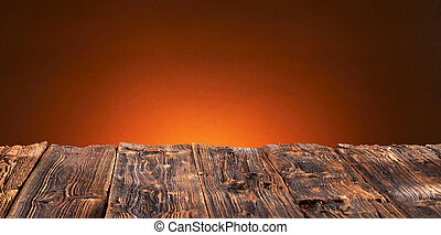Old rustic wooden table top with warm orange glow
