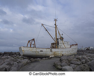 old rusty abandoned fishing boat, ship wreck standing on rock, sea bank promenade in Keflavik, Iceland, blue sky clouds background