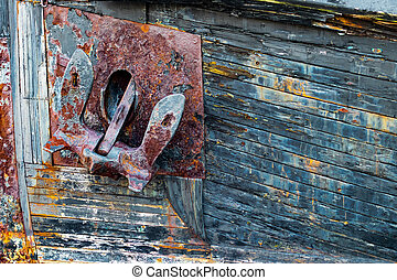 Old rusty anchor on a weathered wooden boat