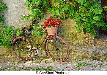 Old rusty bicycle with flowers in a basket