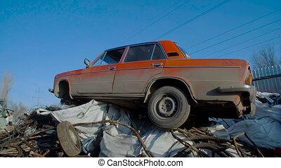 Old Rusty Car in Junkyard Awaits For Recycling. Metal...