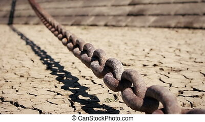 Old rusty chain dangling over the desert ground
