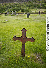 old rusty cross on graveyard - in the grass
