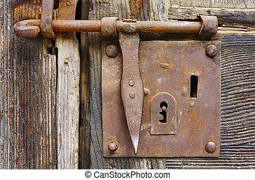 Old rusty door lock on an antique wooden door