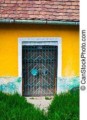 Old rusty door on yellow wall