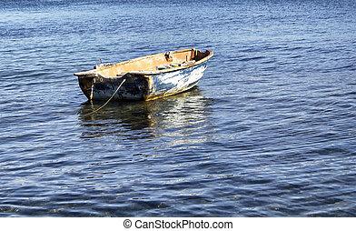 Old, rusty, empty, small boat on Aegean sea in Turkbuku town in Bodrum peninsula.