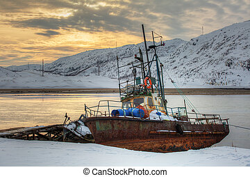 Old rusty fishing boat on the bay at sunset in winter