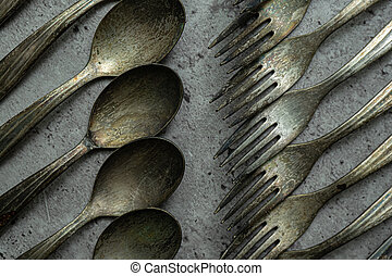 Old rusty forks and spoons on grunge gray background