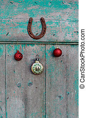Old rusty horseshoe, Christmas toys and vintage clock on wooden door
