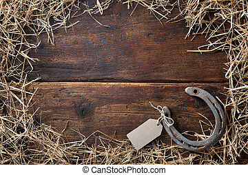 Horseshoe with an empty tag surrounded by straw on vintage wooden board