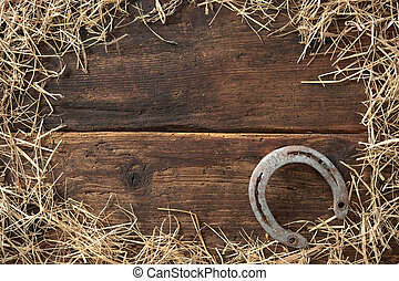 Old rusty horseshoe surrounded by straw on vintage wooden board