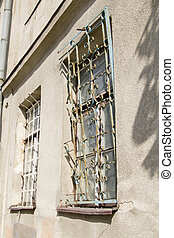 Old rusty iron bars on the window on antique house