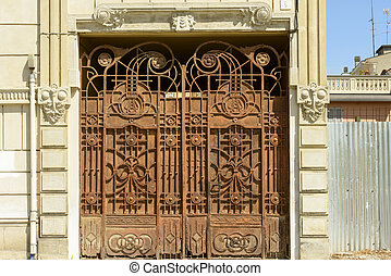 view of old decorated ironwork gate in citycenter of little town, shot in bright light