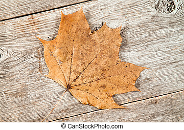 Old rusty leaf on wooden planks