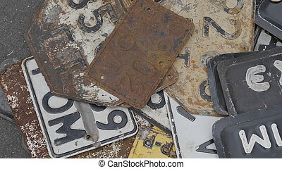 Old rusty license plates of cars.