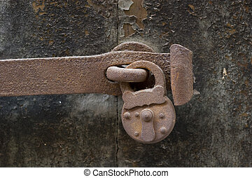 old rusty lock and a bar on an old weathered door