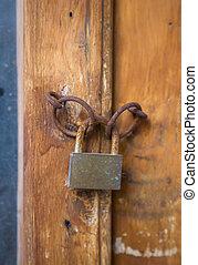 Old rusty lock on wooden door closeup.