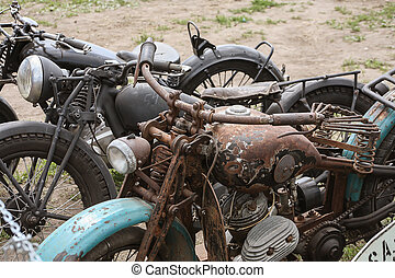 old rusty motorcycles in field closeup