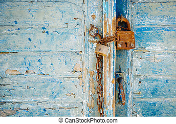 Old rusty padlock and chain on weathered textured door