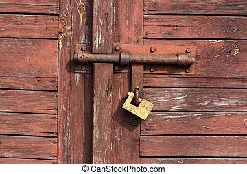 old rusty padlock and hasp on wooden door