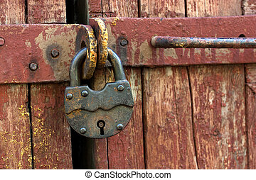 Old rusty padlock in the closed position, hanging on the...