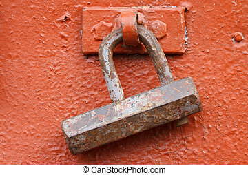 old rusty padlock on a red iron door closeup