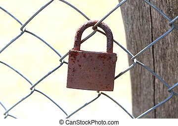 old rusty padlock on an iron fence close-up