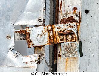 old rusty padlock on broken door