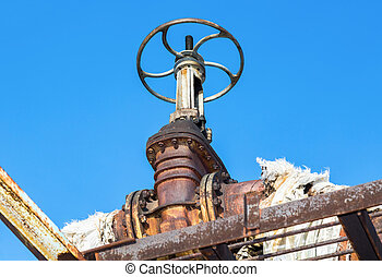 Old rusty pipeline with valve against the blue sky background