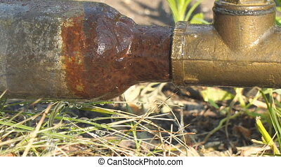 Old rusty pipes and a water tap. Water leakage