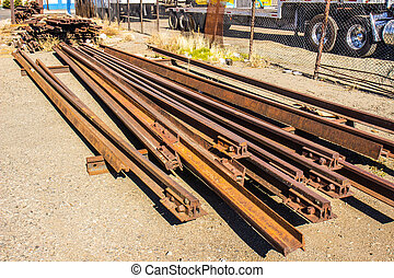 Old Rusty Railroad Rails Stacked By Side of Road