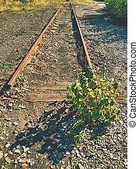 Old rusty rails in abandoned railway station. Rusty train railway detail, granite stones between rails