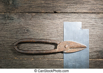 Old rusty scissors on metal on gray planks a background.