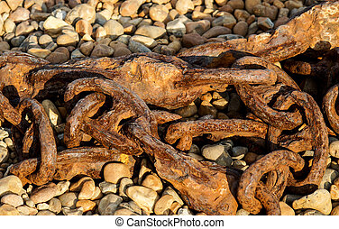 Old rusty ship chain lying on a rocky beach