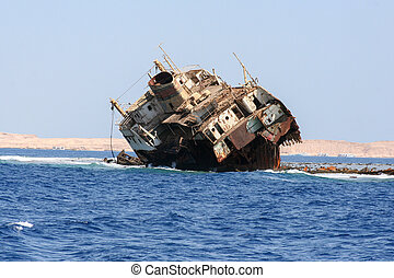 old rusty ship stranded, in the sea, against the background of sandy mountains, Egypt