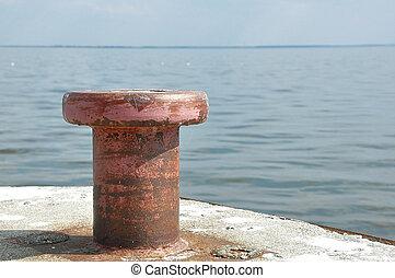 Old rusty steel mooring bollard pole