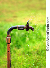 Old rusty tap with water leaking