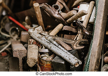 Old rusty tools lie in the shed