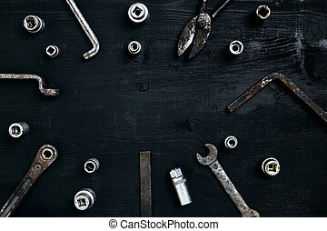 Old, rusty tools lying on a wooden table. Hammer, chisel, metal scissors, wrench, chisel.
