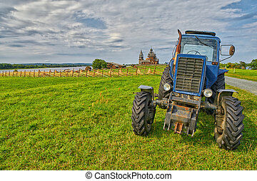 Old rusty tractor on a field with monastery in background