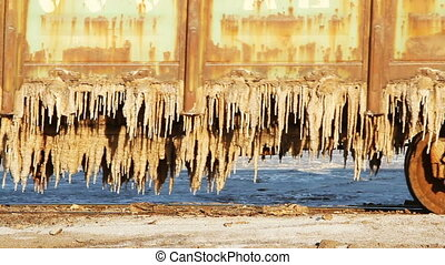 Old rusty train wagons with stalactites of salt at the lake