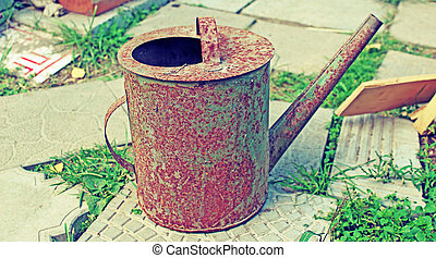 Old rusty watering can in the garden