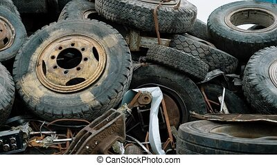 old rusty wheels of different vehicles are dumped in a heap...