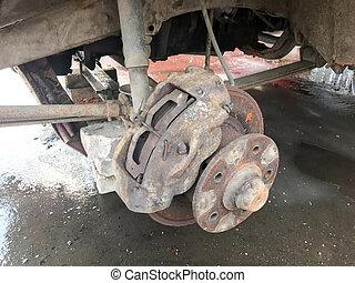 Old rusty worn brake discs, pads of a truck, car. Car suspension repair. Replacing wheel