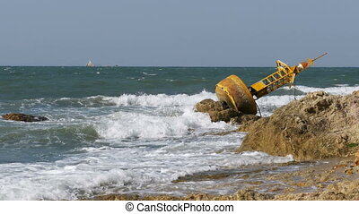 Old Rusty Yellow Buoy Lies on the Shore of a Rocky Beach....